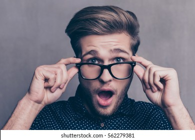 Portrait of shocked young man in glasses with open mouth