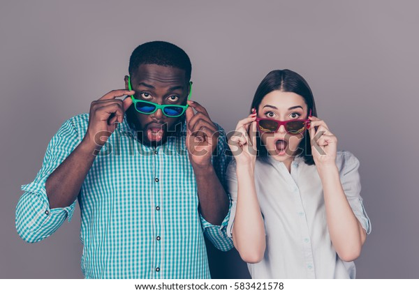Portrait of shocked young multinational couple in love in glasses