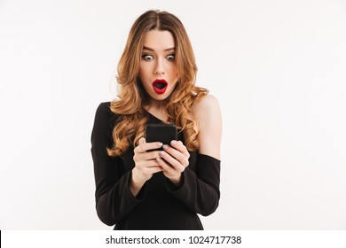 Portrait of a shocked young woman dressed in black dress looking at mobile phone isolated over white background