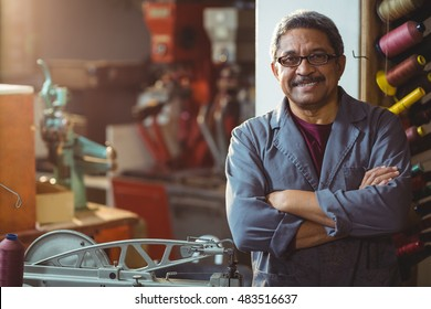 Portrait of shoemaker standing with arms crossed in workshop