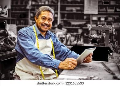 Portrait of shoemaker using digital tablet in workshop