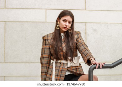 Portrait shooting of a stylish girl. Beige shades. Trends of spring and summer 2019. Bike shorts. Thick cloak, cover jacket. Gold earrings. Heels