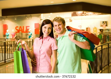 Portrait of shopaholics holding paperbags and smiling at camera