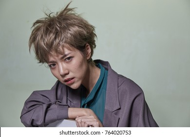 Portrait of short hair Asian girl on light green background.