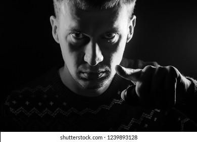 Portrait of a short-haired boy with a shadow on a serious face dressed in a sweater with a monochrome backlight points his finger at the viewer as Uncle Sam on a black isolated background.