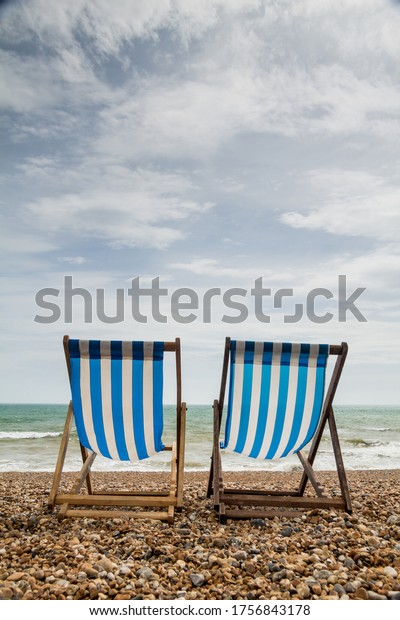 Portrait shot of 2 stripy blue and white deck chairs on an empty shingle beach looking out to sea. Taken in Brighton, England, UK