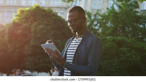Portrait shot of the African American young man in glasses sitting on the banch on the street of a city while watching video on a tablet device and laughing. Indoor.