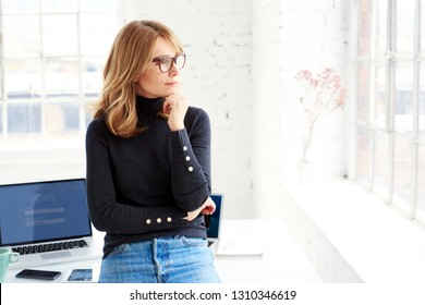 Portrait shot of attractive casual businesswoman deep in thought while standing in the office and looking out the window.