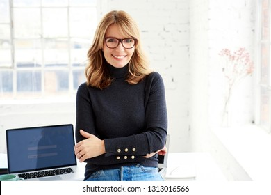 Portrait shot of attractive happy businesswoman standing with folded arms in the office and looking at camera.