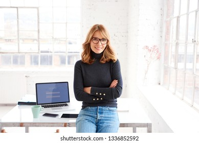 Portrait shot of attractive mature businesswoman in casual clothes standing in the office while looking at camera and smiling.