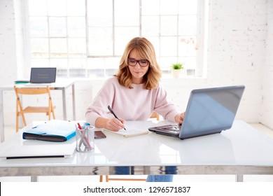 Porträtaufnahme einer attraktiven Geschäftsfrau mittleren Alters, die vor ihrem Laptop sitzt und etwas schreibt, während sie im Büro arbeitet.