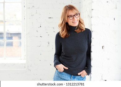 Portrait shot of attractive middle aged woman looking out the window and smiling while standing indoor.