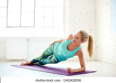 Portrait shot of attractive middle aged woman doing plank exercises on yoga mat in the fitness studio.