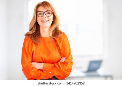 Portrait shot of attractive middle aged businesswoman standing with arms crossed in the office.