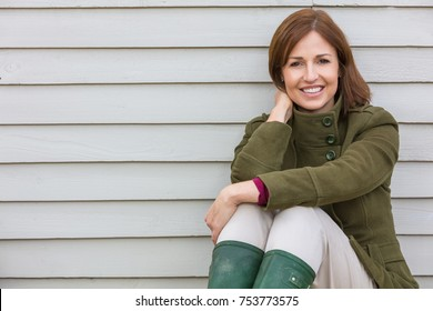Portrait shot of an attractive, single, successful and happy middle aged woman female smiling sitting down outside
