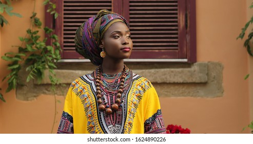 Portrait shot of attractive and stylish young African woman in traditional outfit looking at the side.