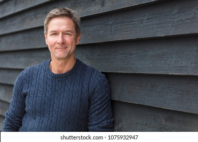Portrait shot of an attractive, successful and happy middle aged man male smiling outside wearing a blue sweater