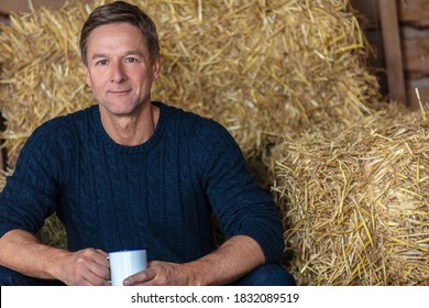 Portrait shot of an attractive, successful and happy middle aged man male wearing a blue sweater sitting on hay bales in a barn or stables drinking cup of tea or coffee