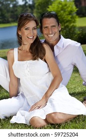 Portrait shot of an attractive, successful and happy middle aged man and woman couple in their thirties, sitting together outside by a lake and smiling.