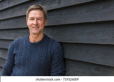 Portrait shot of an attractive, successful and happy smiling middle aged man male outside wearing a blue sweater