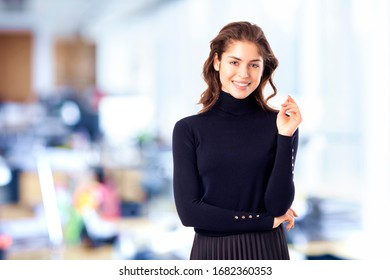 Portrait shot of attractive young businesswoman looking at camera and smiling while standing in the office.