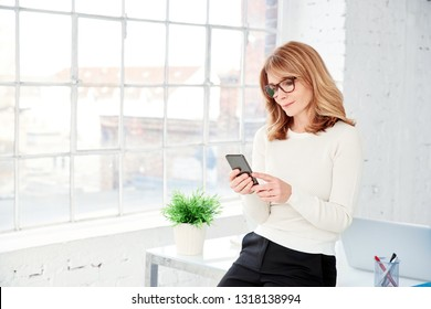Portrait shot of beautiful middle aged businesswoman text messaging while sitting at desk in the office.