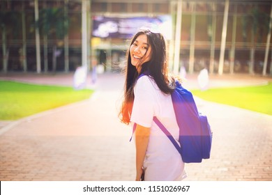 Portrait shot of beautiful young Asian female student smile outdoor with light leaks from the sun in the campus