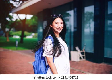 Portrait shot of beautiful young Asian female student smiling outdoor with light leaks from the sun light in the campus