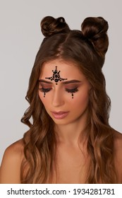 Portrait shot of brown-haired lady with two hair buns and shining patterns of black beads on forehead and under eyes. Temporary tattoos are made as waterproof non-toxic skin stickers.