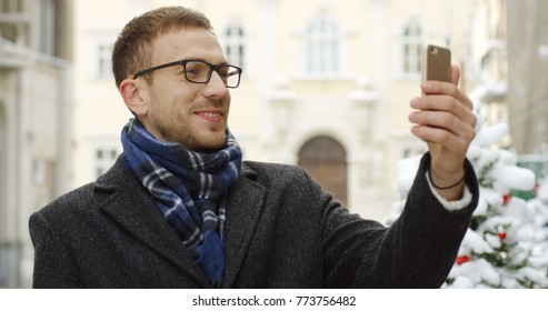 Portrait shot of the caucasian man having video chat in the street of the city center decorated for the Christmas on the snowy winter day. Outdoor