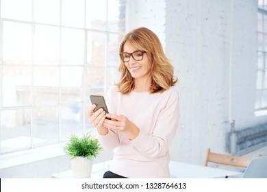 Portrait-Aufnahme von fröhlicher Geschäftsfrau mittleren Alters im Büro und Textnachrichten.