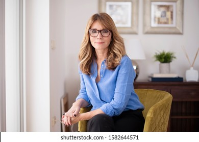 Portrait Aufnahme von selbstbewusster und attraktiver reifer Frau, die Ihnen lächelt, während Sie im Stuhl in der Wohnung sitzen.