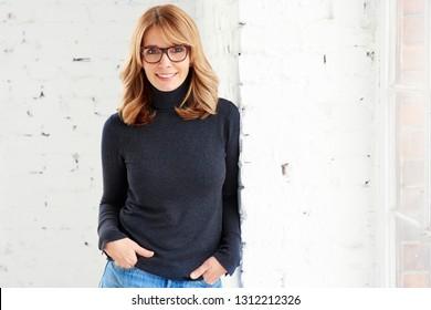 Porträtaufnahme einer selbstbewussten, attraktiven Frau, die die Kamera anschaut und beim Stehen am Fenster lächelt.
