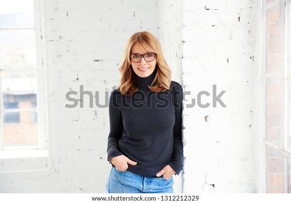 Portrait shot of confident attractive woman looking at camera and smiling while standing at the window.