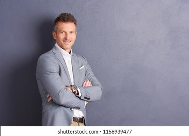 Portrait shot of confident middle aged businessman with folded arms standing at grey wall and looking at camera.