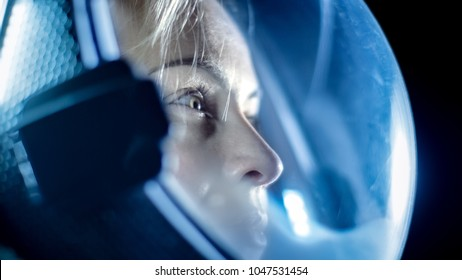 Portrait Shot of the Courageous Female Astronaut  Wearing Helmet in Space, Looking around in Wonder. Space Travel, Exploration and Solar System Colonization Concept.