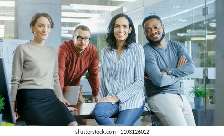 Portrait Shot of a Diverse Group of Talented Young Professionals Sitting on a Desk in the Stylish Modern Environment. Real People Sincerely Smiling on Camera.