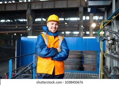 Portrait shot of handsome bearded machine operator wearing reflective vest and hardhat standing at spacious production department of modern plant with arms crossed and looking at camera.