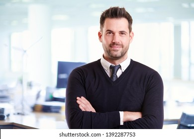 Portrait shot of handsome businessman wearing casual clothes while standing with arms crossed in the office.