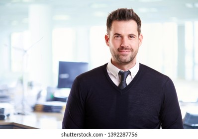 Portrait shot of handsome businessman wearing casual clothes while standing in the office.