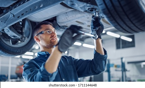 Portrait Shot of a Handsome Mechanic Working on a Vehicle in a Car Service. Professional Repairman is Wearing Gloves and Using a Ratchet Underneath the Car. Modern Clean Workshop.