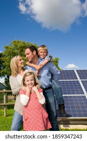 A portrait shot of a happy family standing in front of a large solar panel.