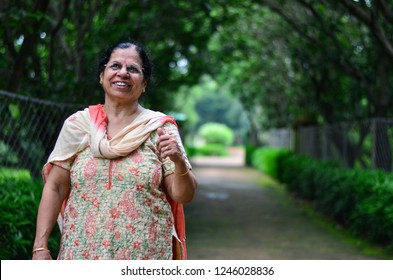 Portrait shot of a happy looking senior north Indian woman wearing traditional Indian salwar kameez pointing upwards in a garden.