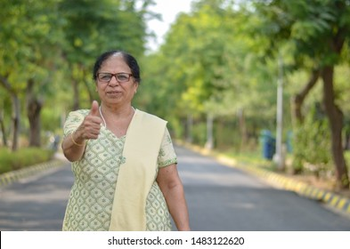 Portrait shot of a happy looking senior north Indian woman wearing traditional chikan kari Indian salwar kameez showing a thumbs up in a garden against a bokeh of canopy of trees.