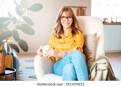 Portrait shot of happy middle aged woman drinking her coffee at home while relaxing in the armchair.