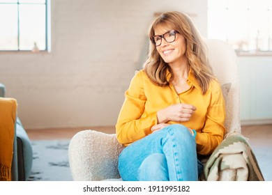 Portrait shot of happy middle aged woman relaxing in the armchair at home.