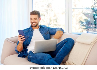 Portrait shot of a happy young man wearing casual clothes while using laptop and text messaging on sofa at home.