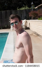 Portrait shot of healthy fit man sitting by the pool with feet in the water with no shirt and blue swim trunks in aviator sunglasses. White shirtless athletic model by outside backyard pool.