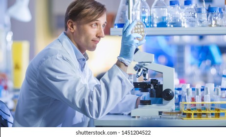 Portrait Shot of a Male Research Scientist in White Coat is Working With a Microscope. He is Looking at Samples in a Modern High-Tech Laboratory. Genetics and Pharmaceutical Studies and Researches.