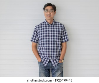 Portrait shot of middle aged asian male model with short black hair wearing blue plaid shirt with stand smiling in front of white stripe background put his hands in jeans pocket.